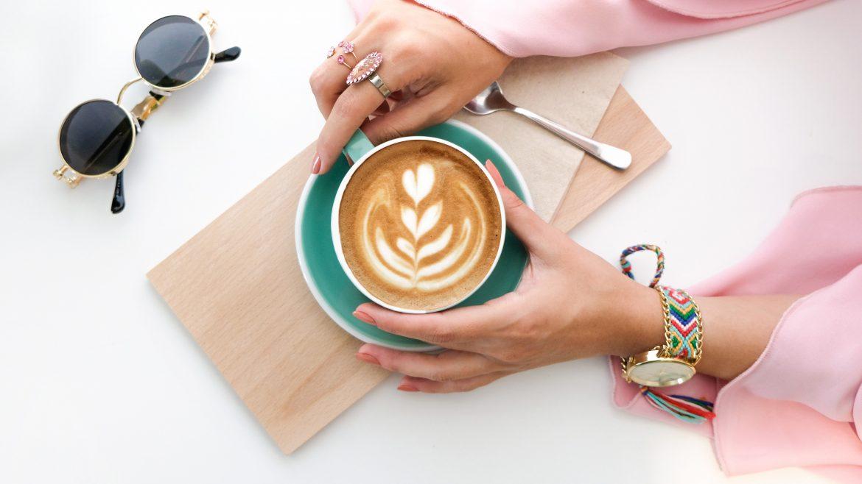 Ilustrasi tangan memegang secangkir kopi di atas meja