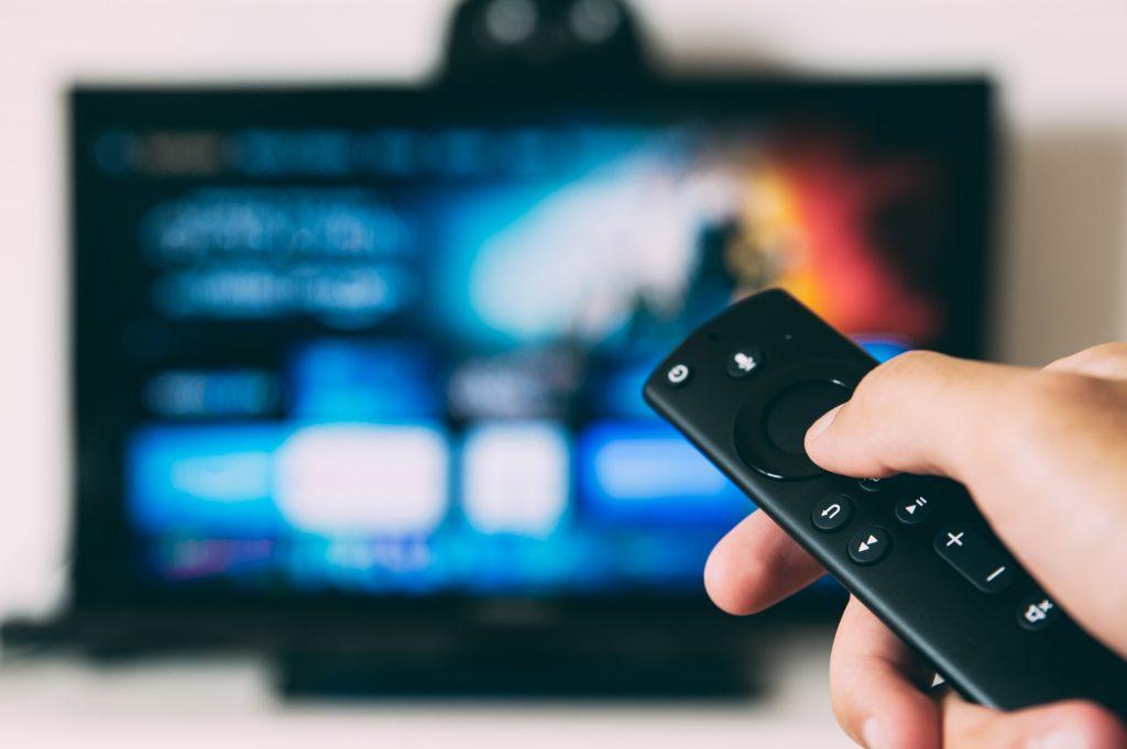 gambar tangan seseorang memegang remote di depan televisi
