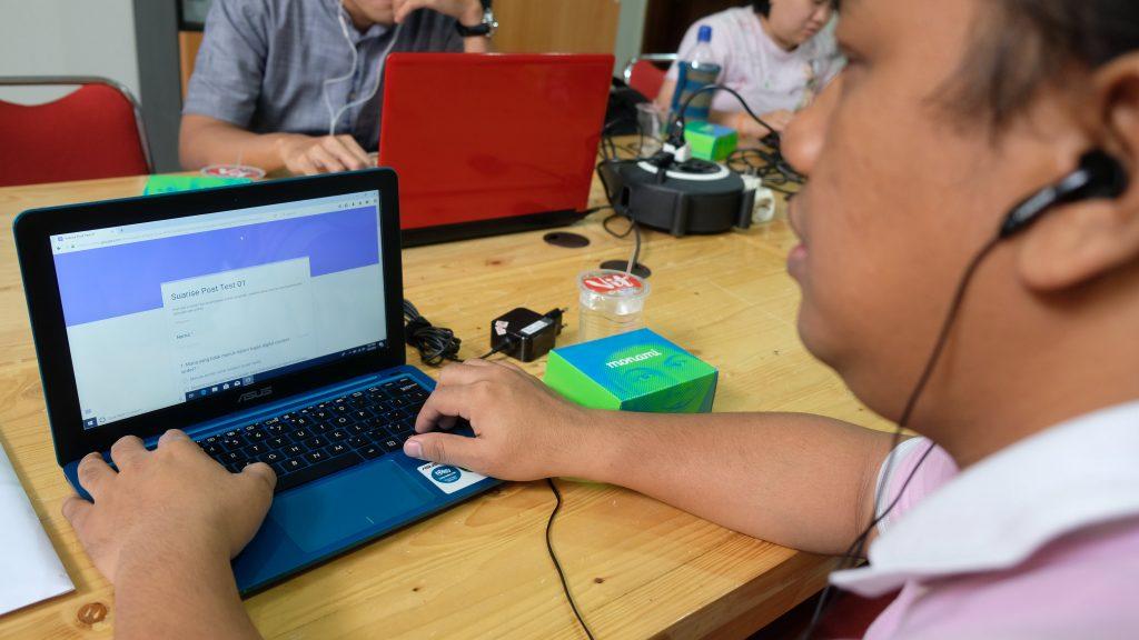 seorang pria tunanetra mengakses Google Form di depan laptop
