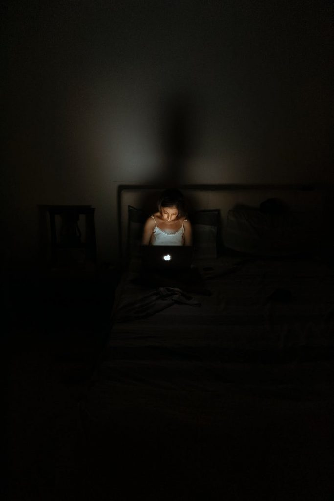 seorang wanita menyalakan laptop di kamar yang gelap